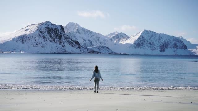 vídeos de stock e filmes b-roll de woman walking on seaside in winter on lofoten island - norte