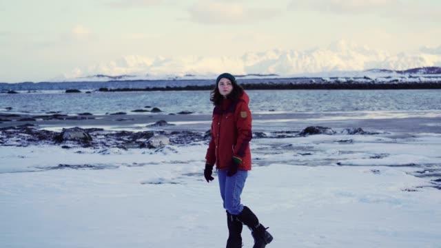 vidéos et rushes de femme marchant sur le bord de mer en hiver sur l'île de lofoten - glacé