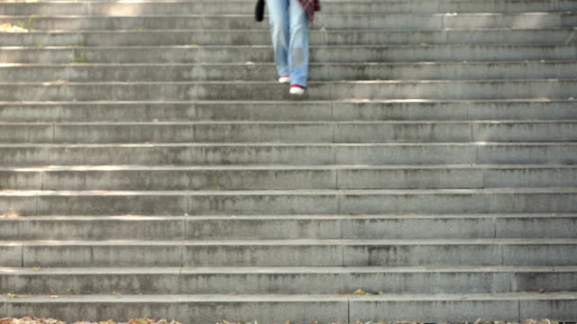 woman walking on stone staircase - scale video stock e b–roll