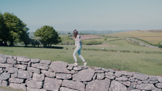 Woman walking on stone wall