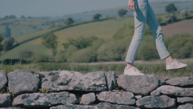 woman walking on stone wall - human leg stock videos & royalty-free footage