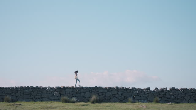 Woman walking on stone wall