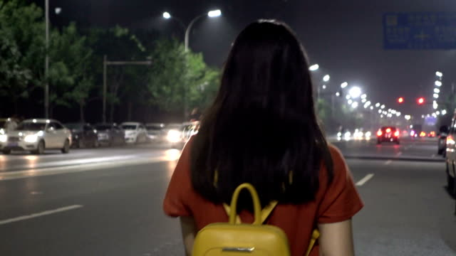 Woman walking on street at night lonely