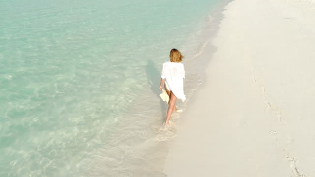 ms woman walking on sunny,idyllic tropical beach,maldives - turquoise coloured stock videos & royalty-free footage