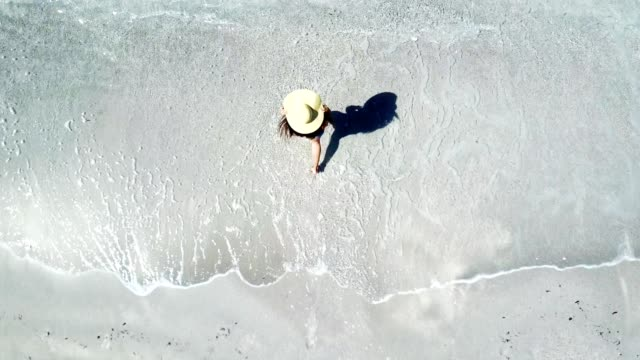 vídeos de stock e filmes b-roll de woman walking on the beach - drone view - chapéu