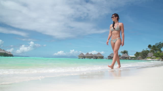 A woman walking on the beach in a bikini lifestyle at a tropical island resort.