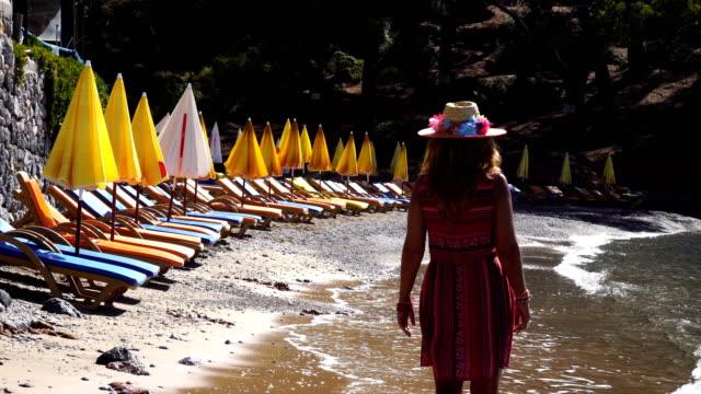 vídeos de stock e filmes b-roll de woman walking on the beach. - só uma mulher madura
