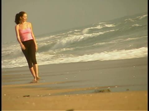 woman walking on the beach - 後ろで束ねた髪点の映像素材/bロール