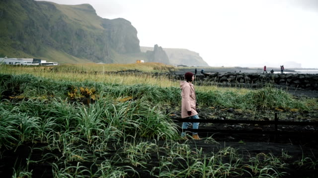 vídeos de stock, filmes e b-roll de mulher andando na praia de areia preta em vik, islândia - capa de chuva