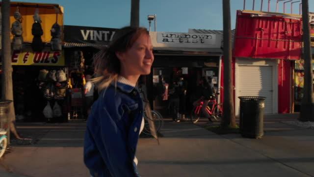woman walking on the boardwalk in venice beach, california - pavement stock videos & royalty-free footage