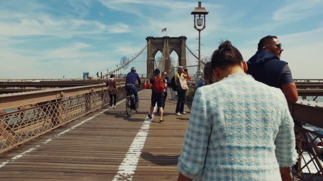 vídeos de stock, filmes e b-roll de mulher caminhando na ponte do brooklyn - brooklyn bridge