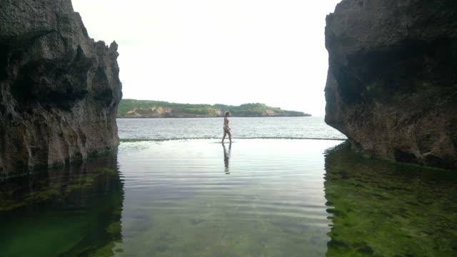 vídeos de stock, filmes e b-roll de mulher que anda na borda da associação natural da infinidade billabong do anjo em nusa penida - lago infinito