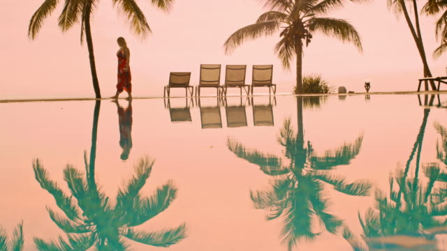 ls woman walking on the edge of the pool at sunset - deck chair stock videos & royalty-free footage
