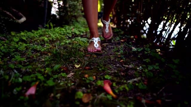 vídeos y material grabado en eventos de stock de mujer caminar en el césped - sandalia