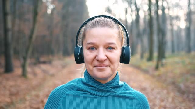 vidéos et rushes de femme de slo mo marchant sur la route à une voie par la forêt d'automne - joggeuse
