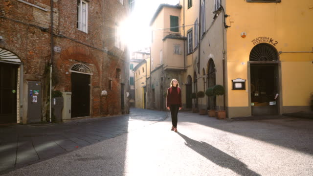 Frau zu Fuß auf den Straßen von Lucca, Italien