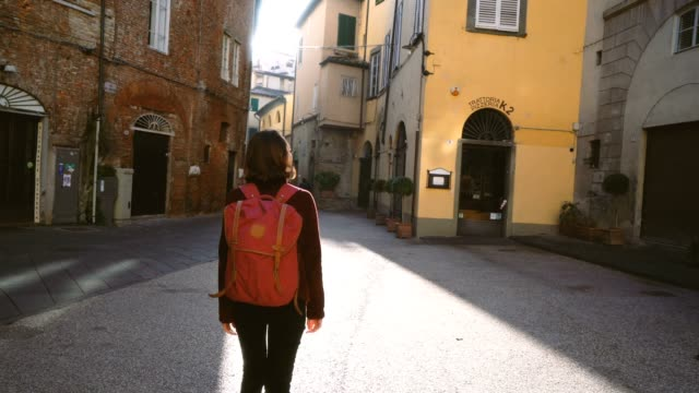 woman walking on the streets of lucca, italy - rucksack stock videos & royalty-free footage