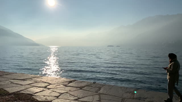 woman walking on the walkway and using phone on waterfront with sunlight and mountain - named wilderness area stock videos & royalty-free footage