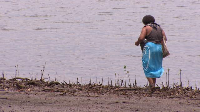 vídeos de stock, filmes e b-roll de woman walking on tidal estuary area near vunidogoloa fiji where coastal waters are encroaching due to climate change - oceano pacífico do sul