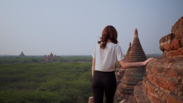frau zu fuß auf stupa und blick auf den malerischen blick auf bagan heritage site - pagode stock-videos und b-roll-filmmaterial