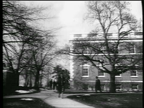 B/W 1944 woman walking on tree-lined path on college campus / industrial