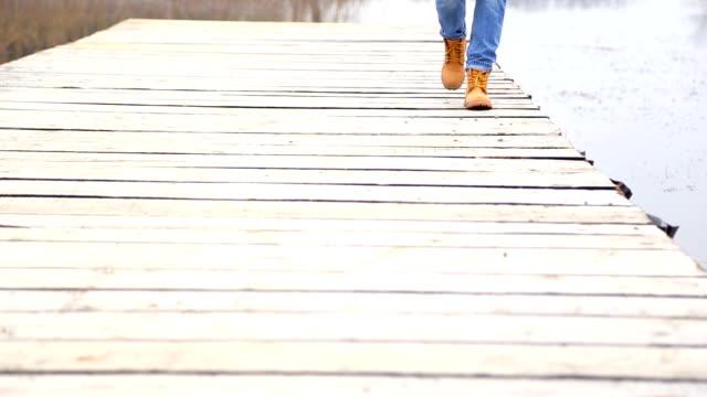 Woman Walking on Wooden Dock