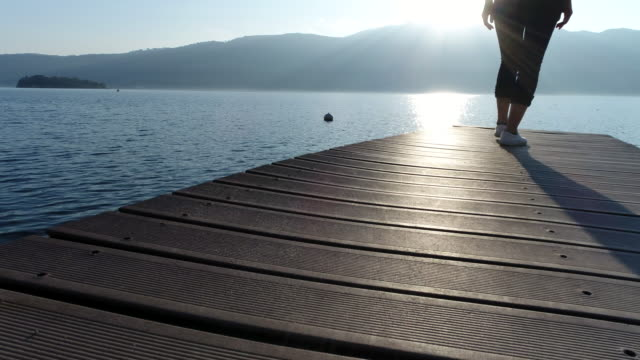 Woman walking on wooden jetty by the lake