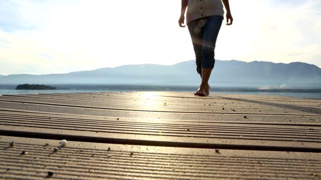 woman walking on wooden pier, cu on feet - jetty stock videos & royalty-free footage