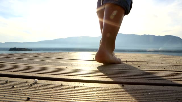 Woman walking on wooden pier, CU on feet