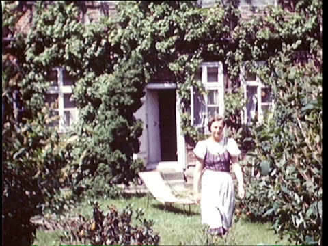 stockvideo's en b-roll-footage met 1937 montage woman walking out from house overgrown with ivy into garden filled with flowers / horst, lower saxony, germany - 1937