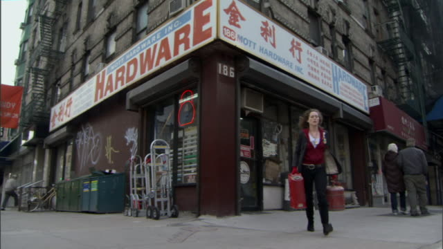 LA WS Woman walking out of corner hardware store carrying two fuel cans / Manhattan, New York, USA