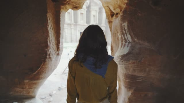 woman walking out of  siq canyon and looking at treasury in petra - esplorazione video stock e b–roll