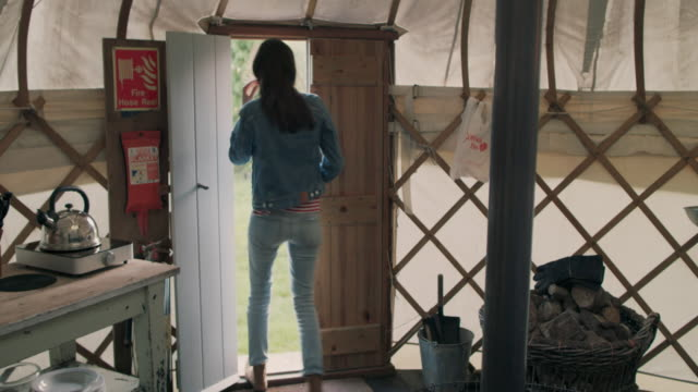 woman walking out of yurt - denim jacket stock videos and b-roll footage