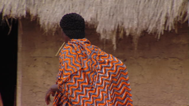 ms r/f cu pan woman walking outside hut while child eating traditional meal, tamale, ghana - ghana stock videos & royalty-free footage