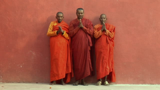 SLO MO WS Woman walking past monks with their hands clasped in prayer / Bodh Gaya, Bihar, India