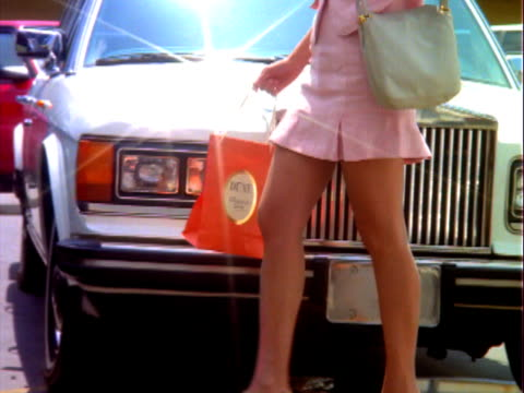 stockvideo's en b-roll-footage met ms pan woman walking past rolls royce / los angeles, california, usa - capital letter