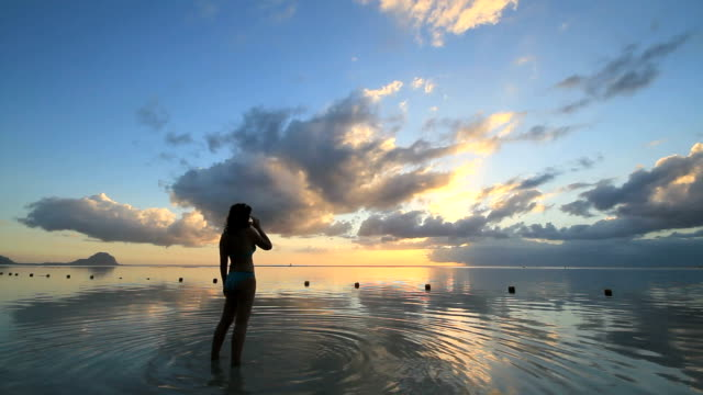 woman walking though water off of beach at sunset - walking in water stock videos & royalty-free footage