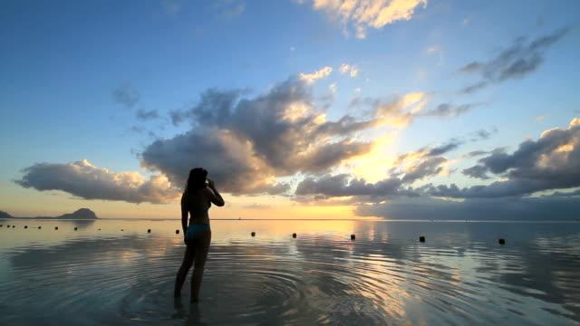 Frau zu Fuß durch Wasser am Strand bei Sonnenuntergang