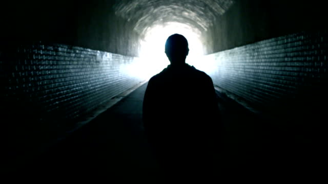 woman walking through a dark tunnel - tunnel stock videos & royalty-free footage