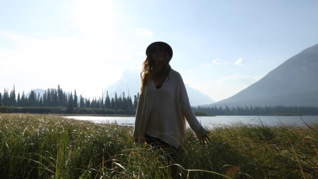 a woman walking through a field of grass during sunrise in banff national park. - meraviglie della natura video stock e b–roll
