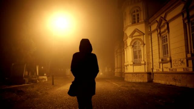vidéos et rushes de femme marchant par une nuit brumeuse - cimetière