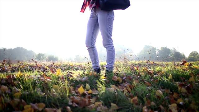 vidéos et rushes de femme marche jusqu'à l'automne laisse sur le sol - jeans texture