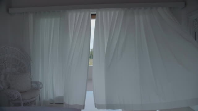 vídeos de stock e filmes b-roll de a woman walking through door and curtains at a villa resort hotel traveling in exotic tropical bali, indonesia. - curtain