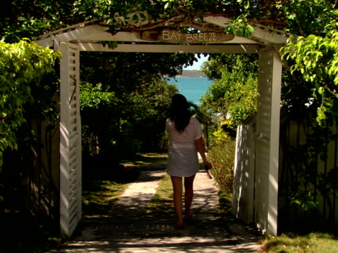 ms,  woman walking through entrance gate on driveway,  rear view,  harbour island,  bahamas - tor konstruktion stock-videos und b-roll-filmmaterial