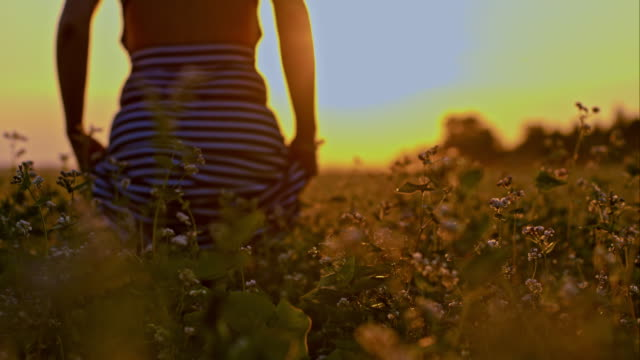 SLO MO Woman walking through field of buckwheat