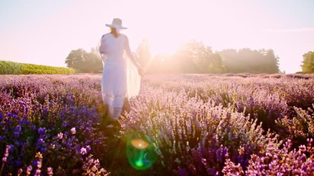 SLO-MO-Frau zu Fuß durch Feld von Lavendelblüten