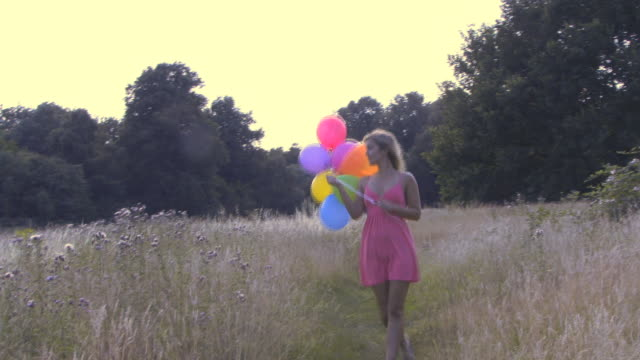 Woman walking through field with balloons; UK