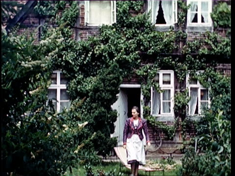 stockvideo's en b-roll-footage met 1937 ws woman walking through garden at from house / horst, lower saxony, germany - 1937