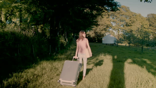 Woman walking through garden with suitcase to yurt