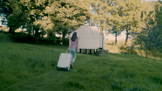 Woman walking through garden with suitcase towards yurt